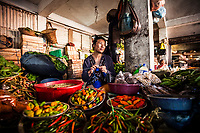 A market seller surrounded by Naga chilis and other produce at her stall in Kohima, the capital of Nagaland, India. Many households keep small chili gardens at home, and the Naga chili sells at the market for around 800 rupees a kilo.