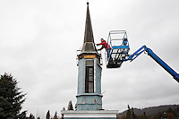 Cody Pearson, owner of Advanced Roofing & Construction, attaches a strap to the steeple of the Lake City Playhouse in Coeur d'Alene in preparation to remove it from the building Tuesday. Pearson is donating about $30,000 in construction services along with other contractors taking part in the renovation project to minimize the cost for the non-profit community theater.