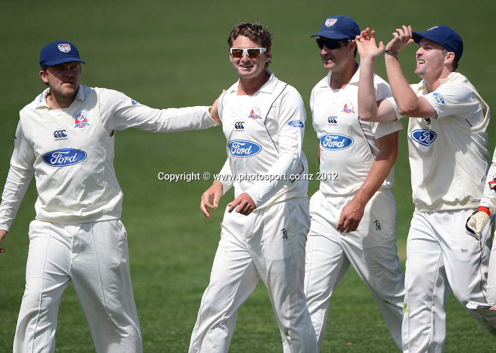 Aces bowler Bruce Martin is congratulated by team mates after Dean Bartlett took a catch to dismiss Anton Devcich. Plunket Shield Cricket, Auckland Aces v Northern Knights at Eden Park outer oval. Saturday 10 November 2012. Photo: Andrew Cornaga/Photosport.co.nz