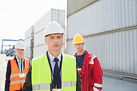 Team of confident workers in shipping yard