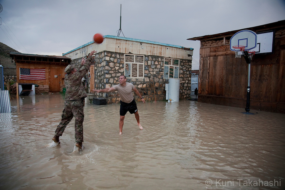 1st SGT Victor Rivera, left, and 1st LT Steve Naser, both of Vaper Company 1/26 Army, play basket ball on flooded court at their COP (Combat Outpost) after heavy rain storm hit the region on Aug 11, 2011 in Khost, eastern Afghanistan..(Photo by Kuni Takahashi)