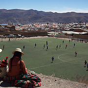 'Attitude at Altitude' Football in Potosi, Bolivia'..Locals play football on the synthetic full size pitch at Miners Stadium, high in the hills in Potosi. The stadium was paid for by miners co operatives, along with help from the President Evo Moralas and his government. 8th May 2010. Photo Tim Clayton..'Attitude at Altitude' Football in Potosi, Bolivia'..The Calvario players greet the final whistle with joyous celebration, high fives and bear hugs the players are sprayed with local Potosina beer after a monumental 3-1 victory over arch rivals Galpes S.C. in the Liga Deportiva San Cristobal. The Cup Final, high in the hills over Potosi. Bolivia, is a scene familiar to many small local football leagues around the world, only this time the game isn't played on grass but a rock hard earth pitch amongst gravel and boulders and white lines that are as straight as a witches nose, The hard surface resembles the earth from Cerro Rico the huge mountain that overlooks the town. .. Sitting at 4,090M (13,420 Feet) above sea level the small mining community of Potosi, Bolivia is one of the highest cities in the world by elevation and sits 'sky high' in the hills of the land locked nation. ..Overlooking the city is the infamous mountain, Cerro Rico (rich mountain), a mountain conceived to be made of silver ore. It was the major supplier of silver for the spanish empire and has been mined since 1546, according to records 45,000 tons of pure silver were mined from Cerro Rico between 1556 and 1783, 9000 tons of which went to the Spanish Monarchy. The mountain produced fabulous wealth and became one of the largest and wealthiest cities in Latin America. The Extraordinary riches of Potosi were featured in Maguel de Cervantes famous novel 'Don Quixote'. One theory holds that the mint mark of Potosi, the letters PTSI superimposed on one another is the origin of the dollar sign...Today mainly zinc, lead, tin and small quantities of silver are extracted from the mine by over 100 co operat