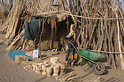 A young girl pushes her wheelbarrow away from a wood stall that supplies building materials and fire timber in the 4 sq km Abu Shouk refugee camp which is (disputedly) home to 38,000 displaced persons and families on the outskirts of the front-line town of Al Fasher (also spelled, Al-Fashir) in north Darfur. .