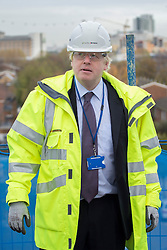 © licensed to London News Pictures. London, UK 25/11/2013. Mayor of London, Boris Johnson helps building an affordable house in Greenwich Square during a photo call before giving a speech on tackling London's housing needs on Monday, November 25, 2013. Photo credit: Tolga Akmen/LNP