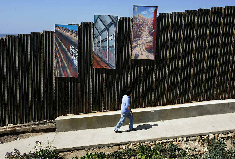 TIJUANA, MEXICO: A visitor walks past paintings affixed to the border wall, which is part of the Jose Parral and Thomas Glassford, insight art installation, in the Las Playas area of Tijuana, Mexico.