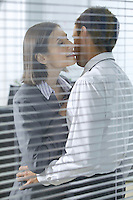 Businesswoman about to kiss businessman in office