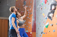 Man and woman discussing by climbing wall in crossfit gym