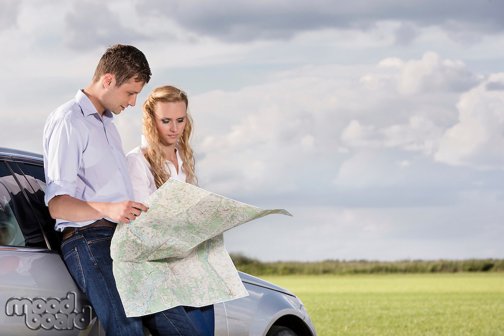 Couple reading map while leaning on car at countryside