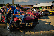 """Deagan and Lilly Foster, 13 and 12 respectively, hang out on their family's shared car before the beginnning of the demolition derby at the Summitt County Fairgrounds, Thursday, July 26, 2016 in Tallmadge, Ohio. Lilly accompanies the family to each race, and is """" ... excited to begin racing next year ... """" when she becomes age-eligible."""