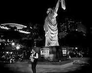 "Taipei man checks his shopping bag in front of a replica of the Statue of Liberty used to promote a credit card company, Taipei, Taiwan.  Taiwan is the only true democracy in the Chinese world (Peoples Republic of China,  Singapore, Hong Kong, & Macau).  Without the backing of a larger democracy, the United States, Taiwan would likely have had ""reunification"" forced upon it long ago, instead of at its own pace and preference."
