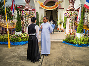 18 SEPTEMBER 2016 - BANGKOK, THAILAND: A priest talks to a girl performing with a high school band at Santa Cruz Church before the church's 100th anniversary mass. Santa Cruz Church was establised in 1769 to serve Portuguese soldiers in the employ of King Taksin, who reestablished the Siamese (Thai) empire after the Burmese sacked the ancient Siamese capital of Ayutthaya. The church was one of the first Catholic churches in Bangkok and is one of the most historic Catholic churches in Thailand. The first sanctuary was a simple wood and thatch structure and burned down in the 1800s. The church is in its third sanctuary and was designed in a Renaissance / Neo-Classical style. It was consecrated in September, 1916. The church, located on the Chao Phraya River, serves as a landmark for central Bangkok.       PHOTO BY JACK KURTZ
