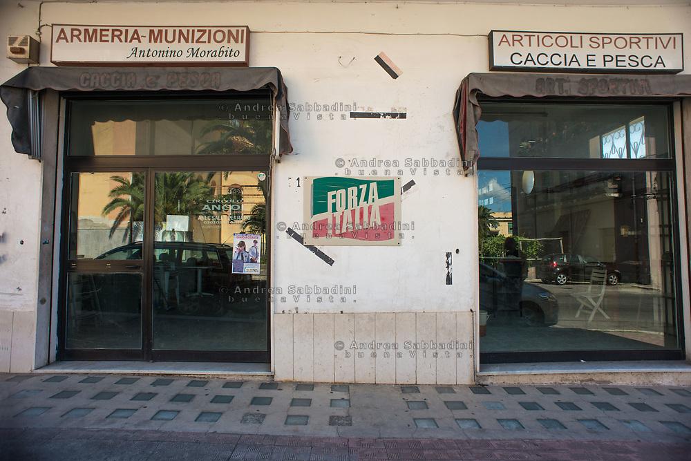 Gioiosa Jonica, 03/07/2017: manifesto Forza Italia tra le vetrine di un' armeria e di un negozio di caccia e pesca.<br /> &copy; Andrea Sabbadini