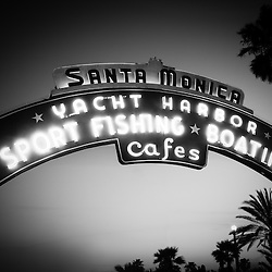 "Santa Monica Pier sign black and white picture. The neon sign is on Colorado Avenue at the entrance of the Santa Monica Pier and says ""Santa Monica Yacht Harbor Sport Fishing Boating Cafes"". Santa Monica Pier is a landmark located in Los Angeles County Southern California and has an amusement park with a ferris wheel, roller coaster, restaurants, and other attractions. Photo is high resolution and was taken in 2012."