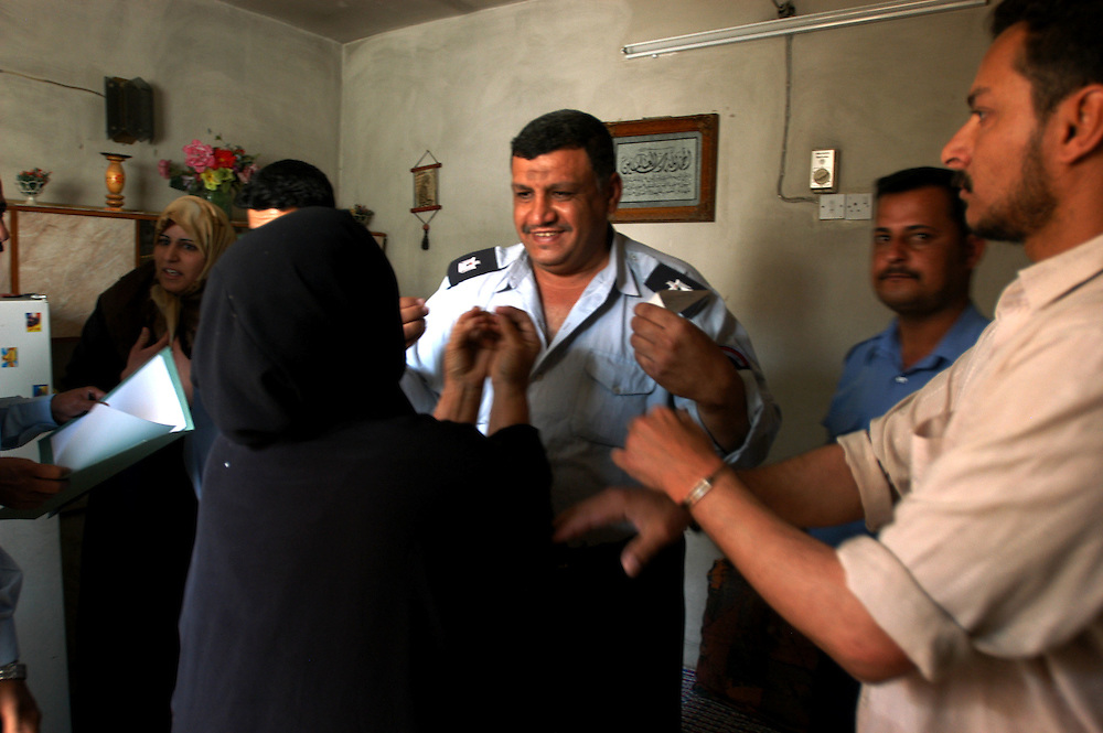 Iraqi Police argue with a woman as they arrest her son who is accused of shooting up the house of his neighbor in order to evict him. The neighbor's daughter was wounded in the shooting..Baghdad, Iraq. 27/04/2004      .Photo © J.B. Russell