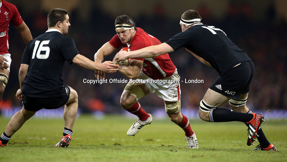24 November 2012 Rugby Union. Wales v New Zealand.<br /> Welsh captain Sam Warburton looks for a gap which is quickly closed by the NZ defence of Coles and Dagg.<br /> <br /> Photo: Mark Leech