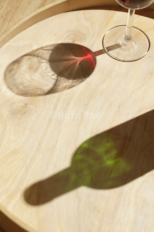 shadow of a wineglass with red wine and a half full bottle on a wooden serving tray