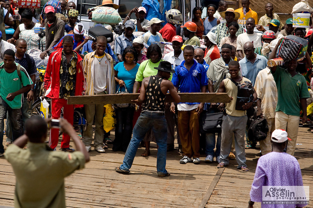 A man tries to control the crowd of passengers on a ferry as it approaches the terminal in Makango, northern Ghana on Thursday March 26, 2009.
