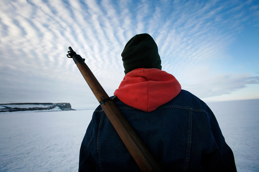 Sasa Samson, 37, the best seal hunter in his community,  drives his snowmobile with a rifle slung on his back on the way to a seal hunt in Resolute Bay, Canada on Tuesday, June 12, 2007.  Sasa often stands next to the breathing hole of the seal without moving for 30 minutes or more to capture the animal with his hooked stick when it rises to the surface to breathe.  Sasa hunts seals for food, and his community uses every part of the seals, either eating the meat or using the hides to make warm clothes.   The traditional way of life in the Resolute Bay Inuit community is being threatened by rising temperatures.  The dangers of global warming, which have been extensively documented by scientists, are appearing first, with rapid, drastic effects, in the Arctic regions where Inuit people make their home.  Inuit communities, such as those living on Resolute Bay, have witnessed a wide variety of changes in their environment.  The ice is melting sooner, depleting the seal population and leaving them unable to hunt the animals for as long.  Other changes include seeing species of birds and insects (such as cockroaches and mosquitoes) which they have never encountered before.  The Inuit actually lack words in their local languages to describe the creatures they have begun to see.....