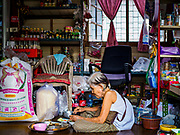 "21 JUNE 2017 - BANGKOK, THAILAND: A woman eats lunch in her shop in a community along the Chao Phraya River south of Krung Thon Bridge. This is one of the first parts of the riverbank that is scheduled to be redeveloped. The communities along the river don't know what's going to happen when the redevelopment starts. The Chao Phraya promenade is development project of parks, walkways and recreational areas on the Chao Phraya River between Pin Klao and Phra Nang Klao Bridges. The 14 kilometer long promenade will cost approximately 14 billion Baht (407 million US Dollars). The project involves the forced eviction of more than 200 communities of people who live along the river, a dozen riverfront  temples, several schools, and privately-owned piers on both sides of the Chao Phraya River. Construction is scheduled on the project is scheduled to start in early 2016. There has been very little public input on the planned redevelopment. The Thai government is also cracking down on homes built over the river, such homes are said to be in violation of the ""Navigation in Thai Waters Act."" Owners face fines and the possibility that their homes will be torn down.          PHOTO BY JACK KURTZ"