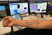 The right forearm of one of the LIGO scientists, Corey Gray, sports a real tatoo of the gravitational wave as detected by the Hanford (WA) and Livingston (LA) observatories. Shown at the control room at Laser Interferometer Gravitational Observatory ; Hanford, Washington near Richland WA<br /> &copy;Rich Frishman/ALL RIGHTS RESERVED