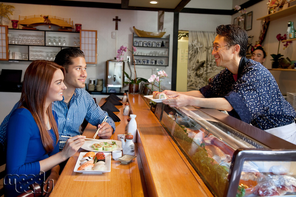 Asian chef serving sushi to young couple in restaurant