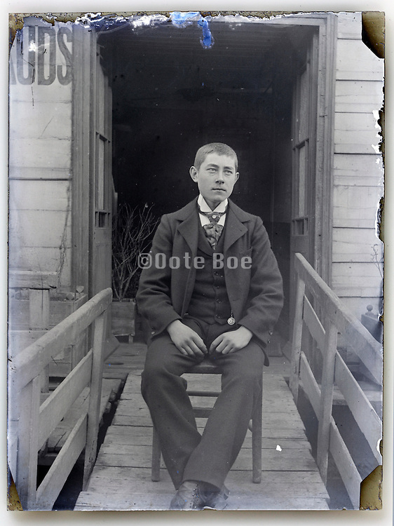 young adult man sitting on the bridge to houseboat Paris early 1900s