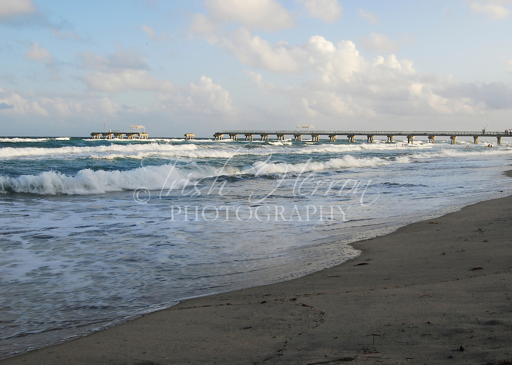 Waves break on the beach in front of a broken pier in Lake Worth, Florida.