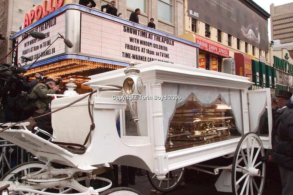 This is the funeral procession of singer James Brown which was held in Harlem on on Dec. 28, 2006. Brown's gold casket was carried by horse drawn carriage from Reverend Al Sharpton National Action Network (NAN) on W. 145th, down Malcolm X Boulevard (Lenox Ave.) to the Apollo Theater and was followed closely behind by Rev. Sharpton and thousands of spectators. The Godfather of Soul's body was to lay in repose later in the day from 1-8 PM at the Apollo. This view shows the carriage containing Brown's casket just after the procession came to a halt in front of the Apollo.