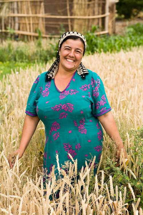 Classic Uzbek woman showing off her (wheat) garden with pride, near Khiva
