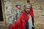 A U.S. Navy Civil Affairs soldiers searches an Afghan villager during a patrol.
