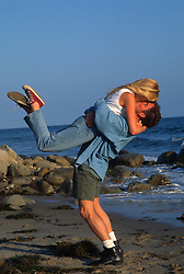 Man lifting girl up and kissing her while on the beach in California
