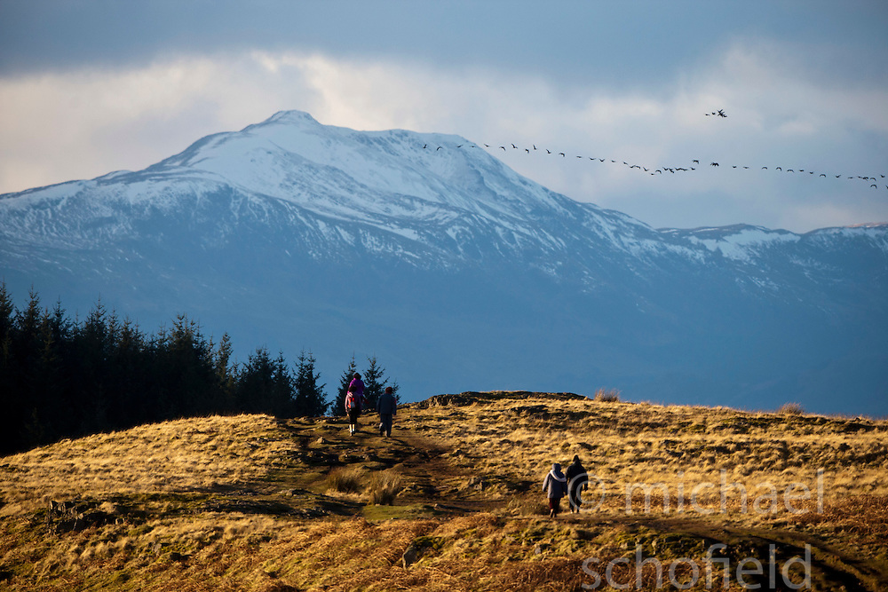 Walkers in the afternoon sunlight on the slope of the Dumyat, a hill at the western extremity of the Ochil Hills, in central Scotland. .Pic © Michael Schofield...
