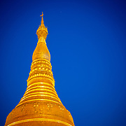 Top detail of the ornately covered The Shwedagon Pagoda, officially named Shwedagon Zedi Daw and also known as the Great Dagon Pagoda and the Golden Pagoda, is a gilded stupa located in Yangon, Myanmar.