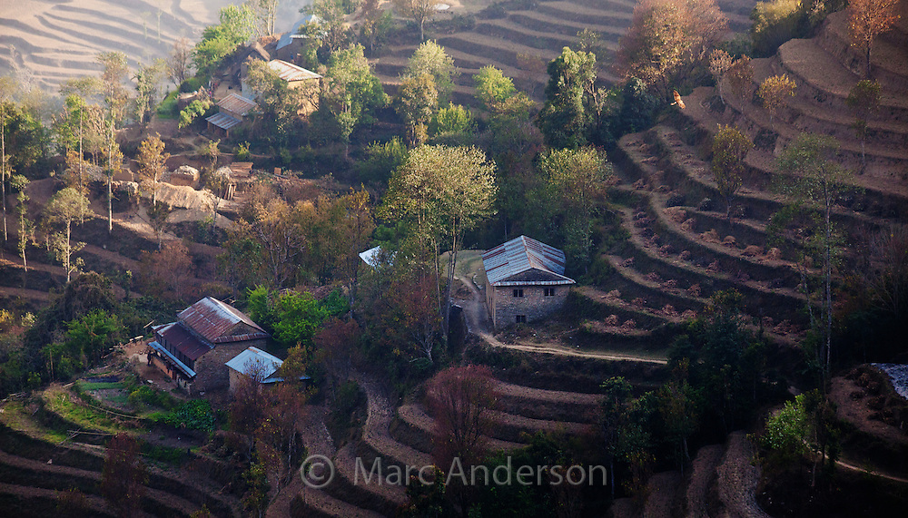 Warm afternoon sunlight hitting a small village and terraced fields on the foothills of the Himalayas, near Kutumsang, Helambu Region, Nepal