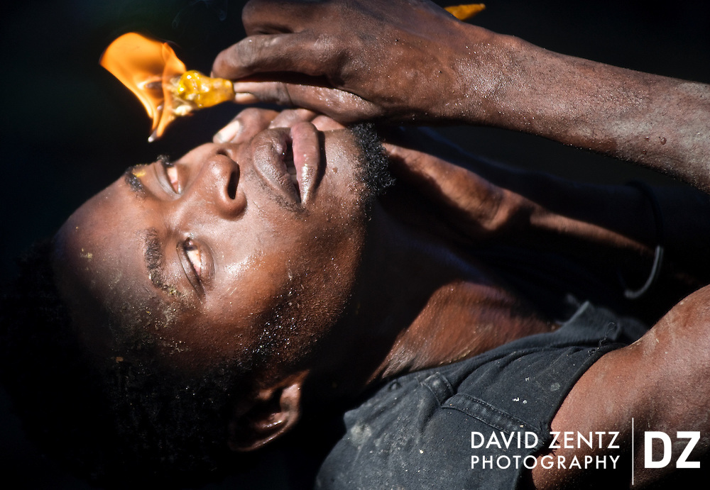 A young pilgrim brings a lit candle close to his eye while tracing the flame across his body during the voodou festival at Plaine du Nord, in northern Haiti, on July 24, 2008.