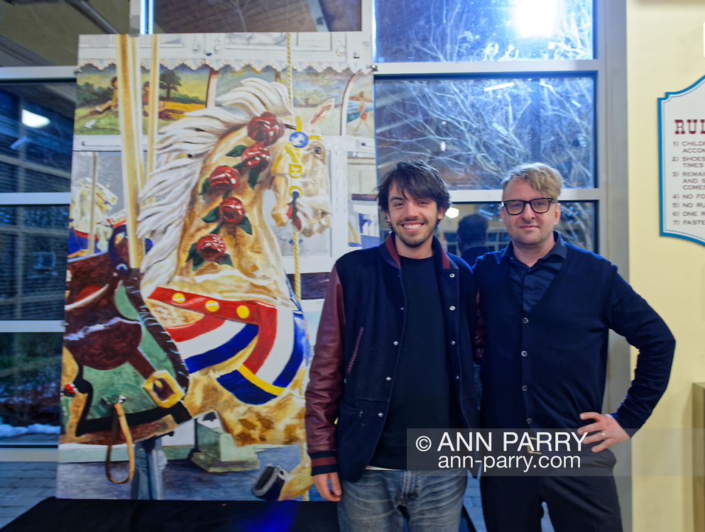 Garden City, New York, USA. March 9, 2019.  R-L, Artists MICHAEL WHITE and LIAM MCGUIRE, of Baldwin, who said White is his mentor and friend, are posing next to  White's mural of closeup of Nunley's Carousel lead horse. The Unveiling Ceremony of mural was held at historic Nunley's Carousel in its Pavilion on Museum Row on Long Island.