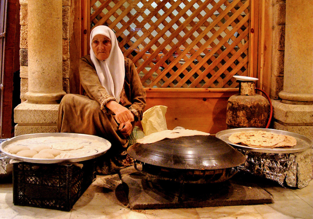 Old Woman Toasting Shrak or Bedouin Bread on Saj Hot Griddle in Jerash, Jordan<br />