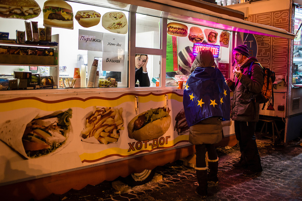 KIEV, UKRAINE - DECEMBER 11: A woman wrapped in a European Union flag stops at a hot dog stand near Independence Square on December 11, 2013 in Kiev, Ukraine. Thousands of people have been protesting against the government since a decision by Ukrainian president Viktor Yanukovych to suspend a trade and partnership agreement with the European Union in favor of incentives from Russia. (Photo by Brendan Hoffman/Getty Images) *** Local Caption ***