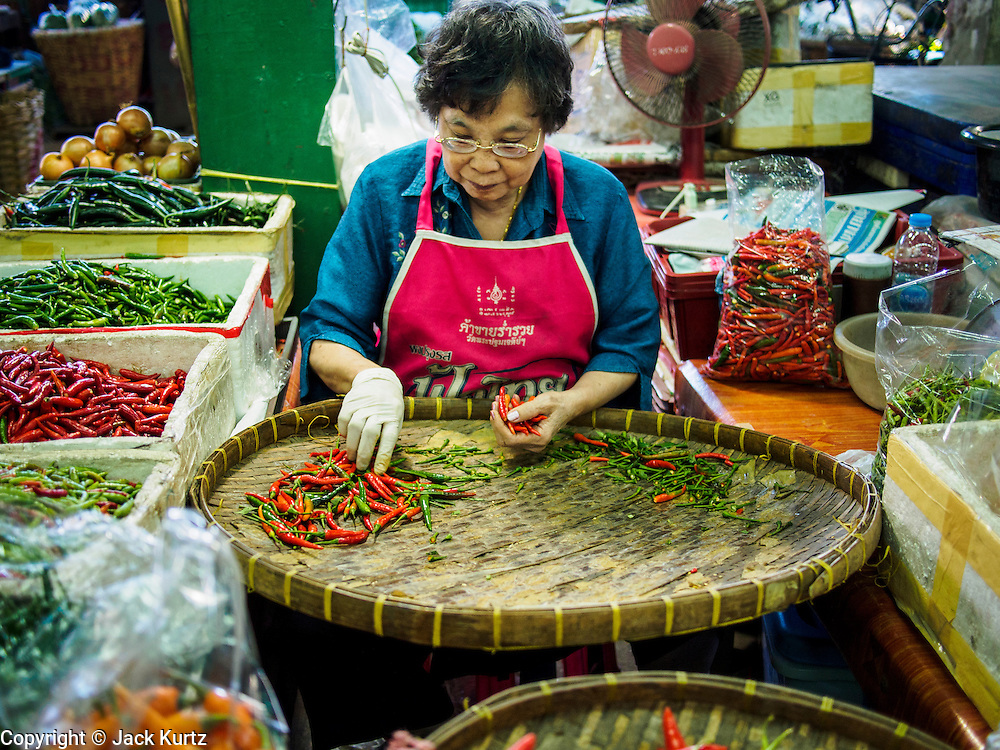 "19 DECEMBER 2013 - BANGKOK, THAILAND:    A woman sorts chilies for sale in the flower market. Pak Khlong Talat (""the market at the mouth of the canal"") is a market in Bangkok that sells flowers, fruits, and vegetables. It is the primary flower market in Bangkok. It is located on Chak Phet Road and adjacent side-streets, close to Memorial Bridge. The market is open 24 hours, but is busiest before dawn, when boats and trucks arrive with flowers from nearby provinces.       PHOTO BY JACK KURTZ"