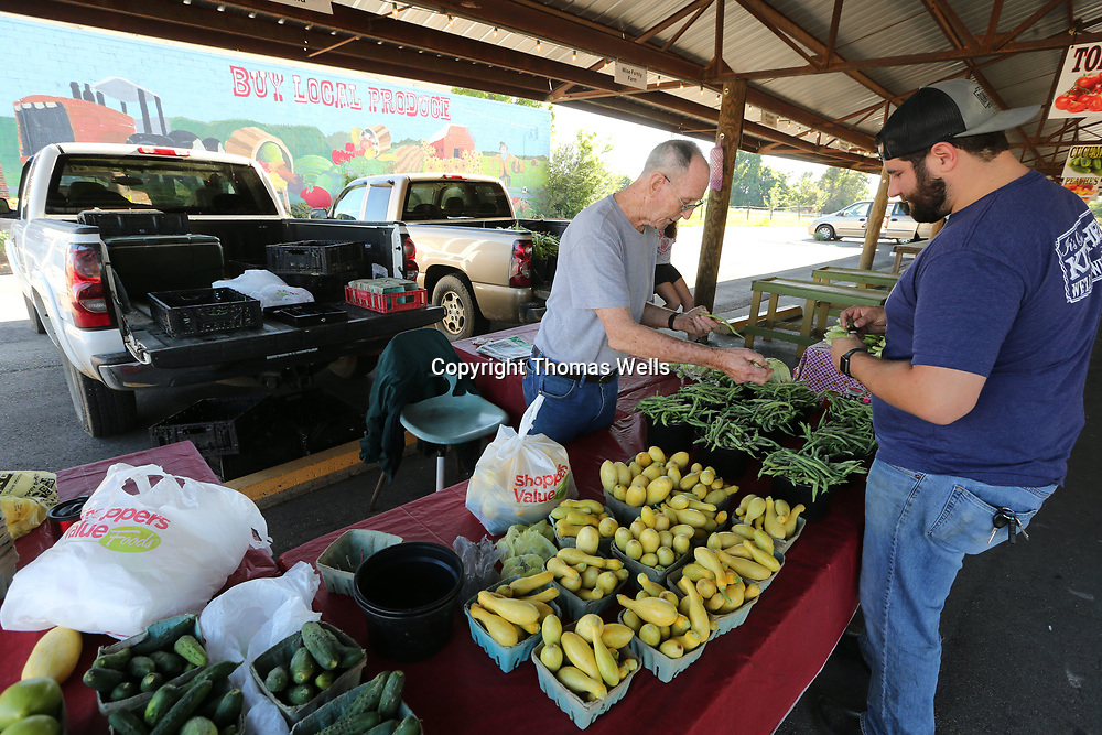 Jimmy Sheffield, left, of Mooreville bags up the vegetables for Romie's Grocery Kitchen Manager Corbin Boyd at Thursday's farmer's market at the Farmer's Depot in Tupelo.