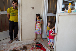 © Licensed to London News Pictures. Hamdaniyah, Iraq. 26/07/2014.  Iraqi Christian refugee Dilar Minowar Salim, 9 (C), watches as her family receives fresh drinking water from Kurdish Zeravani soldiers at the partially built home she shares with 16 other family members in Hamdaniyah, Iraq. Dilar left Mosul on Friday the 18th of July with her family when Islamic State fighters issued an ultimatum to the city's Christian community. When the family left they were forced to pay a tax for their car, and her elder brother (19) was threatened at knifepoint to ensure they handed over all of their possessions including family photographs.<br /> <br /> <br /> Having taken over Mosul Iraq's second largest city in June 2014, fighter of the Islamic State (formerly known as ISIS) have systematically expelled the cities Christian population. Despite having been present in the city for more than 1600 years, Christians in the city were given just days to either convert to Islam, pay a tax for being Christian or leave; many of those that left were also robbed at gunpoint as they passed through Islamic State checkpoints.. Photo credit : Matt Cetti-Roberts/LNP