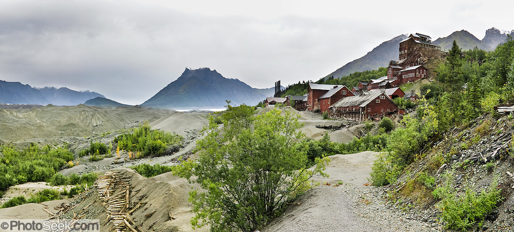 """Kennecott Concentration Mill rises 14 stories tall beside Kennicott Glacier beneath Bonanza Ridge in the Wrangell Mountains, Alaska, USA. Kennecott Mines National Historic Landmark and nearby McCarthy lie within Wrangell-St. Elias National Park and Preserve, the largest National Park in the USA. Old mine buildings, artifacts, and colorful history attract summer visitors. Remote McCarthy is connected to Chitina via the McCarthy Road spur of the Edgerton Highway. At the east end of McCarthy Road, visitors must park their vehicle and walk across the footbridge to McCarthy. From McCarthy, a privately-operated shuttle takes visitors 5 miles to Kennecott. After copper was discovered between the Kennicott Glacier and McCarthy Creek in 1900, the Kennecott town, mines, and Kennecott Mining Company were created and named after the adjacent glacier. Kennicott Glacier and River had previously been named after Robert Kennicott, a naturalist who explored in Alaska in the mid-1800s. The corporation and town stuck with a mistaken spelling of """"Kennecott"""" with an e (instead of """"Kennicott"""" with an i). Partly because alcoholic beverages and prostitution were forbidden in the company town of Kennecott, the neighboring town of McCarthy grew quickly to provide a bar, brothel, gymnasium, hospital, and school. The Copper River and Northwestern Railway reached McCarthy in 1911 to haul over 200 million dollars worth of ore 196 miles to the port of Cordova on Prince William Sound. By 1938, the worlds richest concentration of copper ore was mostly gone, the town was mostly abandoned, and railroad service ended. Not until the 1970s did the area began to draw young people for adventure and the big money of the Trans Alaska Pipeline project. Declaration of Wrangell-St. Elias National Park in 1980 drew adventurous tourists who helped revive McCarthy with demand for needed services. Wrangell-St. Elias National Park and Preserve is honored by UNESCO as a World Heritage Site."""