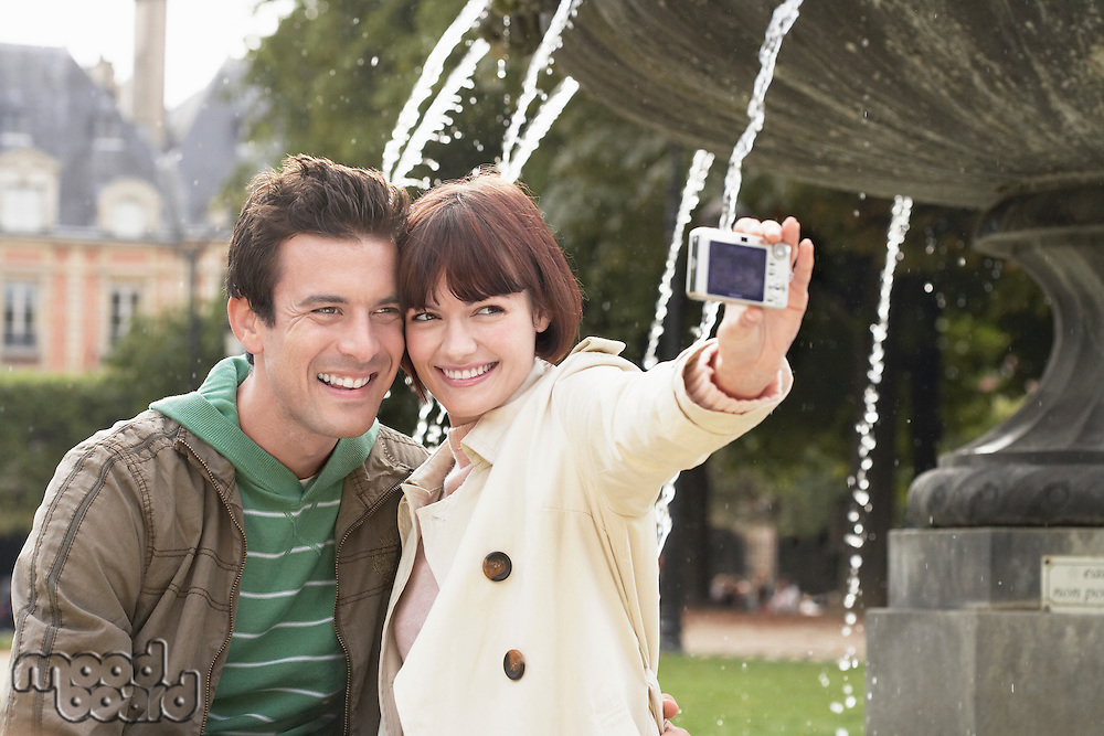 Couple photographing themselves in front of fountain