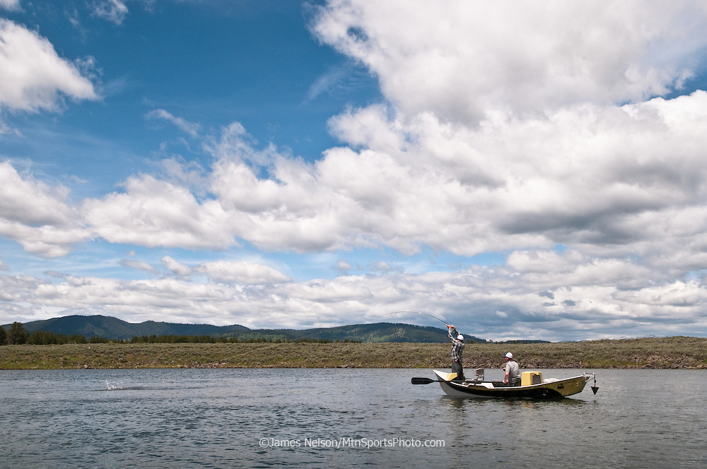 An angler in a drift boat plays a rainbow trout on the upper Henry's Fork of the Snake River, Idaho.