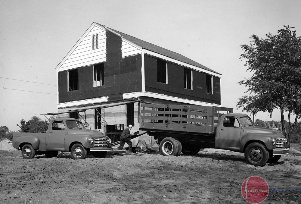 Two Studebaker 2R-Series trucks at a home construction site.