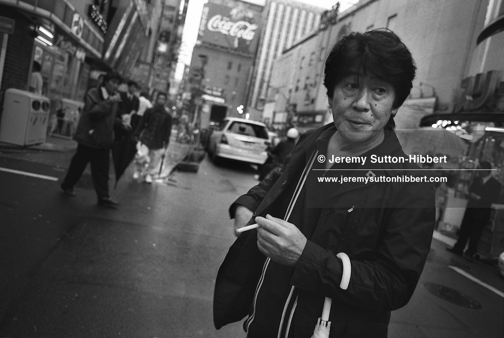 Daido Moriyama, one of the most famous photographers in Japan, photographed in the Kabukicho red light district of Shinjuku, Tokyo, Japan, 2003.  Born in Osaka in 1938. Famous for his grainy gritty street photography, author of books such as 'New York' and most recently 'Shinjuku'. Soon to have exhibition in Paris, October 2003, and Shine Gallery, London, February 2004.