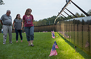 "From left, John McNeely, a member of the OHIO Parents Advisory Council, Katie McNeely, a senior studying child and family studies at Ohio University, and Lori Guthrie, an Athens resident, look at ""The Wall That Heals"", a half-scale replica of the Vietnam Veterans Memorial, in Bicentennial Park on September 15, 2017."