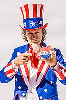 Uncle Sam holding a vote pin and pointing at it telling you to vote.