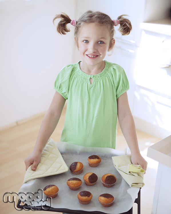 Young girl holding baking tray in kitchen