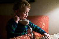 A 2-year-old boy plays with a telephone in his family's home.